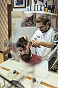 Barber cutting hair of a customer - MGOF000895