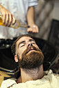 Barber washing hair of a customer - MGOF000898