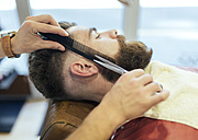 Barber cutting beard of a customer - MGOF000910