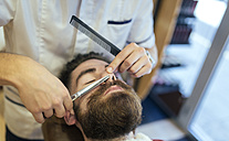 Barber cutting beard of a customer - MGOF000913