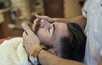 Barber adjusting beard of a customer - MGOF000916