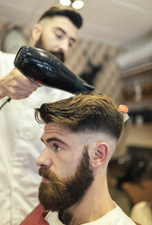 Barber blow-drying hair of a customer - MGOF000919