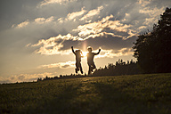 Silhouettes of two children jumping side by side on a meadow at backlight - SARF002234
