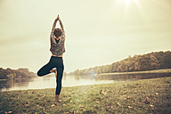 Woman holding a Vrksasana yoga pose in autmny park - MFF002443