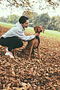 Woman talking to her Vizsla dog in park during autumn - MFF002455