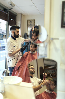 Two barbers cutting hair of twin brothers in barber shop - MGOF000926