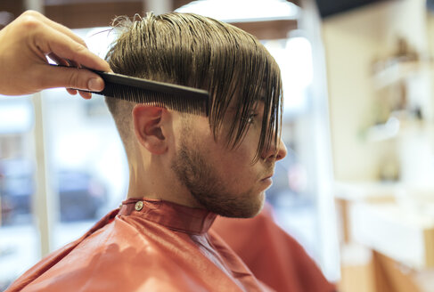 Barber combing hair of a customer - MGOF000932