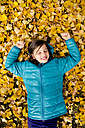 Smiling girl lying on ground covered with autumn leaves - LVF004043