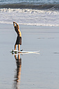 Indonesia, Bali, surfer stretching on the beach - KNTF000134
