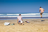 Indonesia, Bali, two surfers doing exercises on the beach - KNTF000137