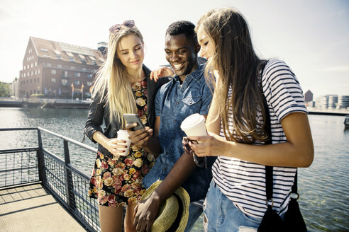 Germany, Duisburg, three young people looking at smartphone at Media Harbour - GDF000883
