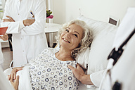 Senior woman in hospital talking to doctors, smiling - MFF002463