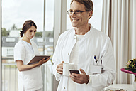 Doctor with coffee cup and smartphone, nurse working in background - MFF002481