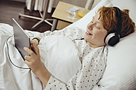 Sick boy lying in hospital using digital tablet, wearing head phones - MFF002490