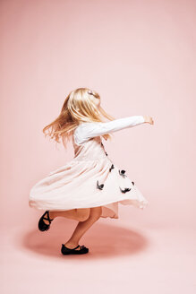 Little girl dancing in front of pink background - IPF000263