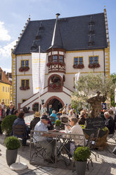 Germany, Lower Franconia, Volkach, People sitting in cafe at he marketplace with town hall in background - SIE006827