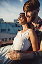 Austria, Vienna, Young couple enjoying romantic sunset on rooftop terrace - AIF000120