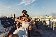 Austria, Vienna, Young couple enjoying romantic sunset on rooftop terrace - AIF000123