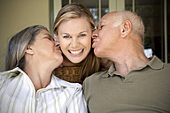 Portrait of smiling woman with  parents kissing her - RMAF000018