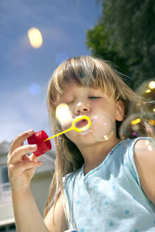 Portrait of little girl blowing soap bubbles - RMAF000024
