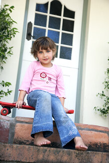 Portrait of little girl sitting on a  skateboard - RMAF000045