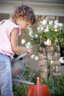 Little girl with watering can in the garden - RMAF000057