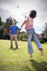 Little girl playing badminton with her grandfather - RMAF000060