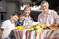 Family portrait of little boy and girl with their grandparents sitting at dining table in the garden - RMAF000075