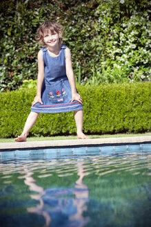 Smiling little girl standing at pool edge - RMAF000078