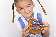 Portrait of smiling little girl with pretzel - YFF000470