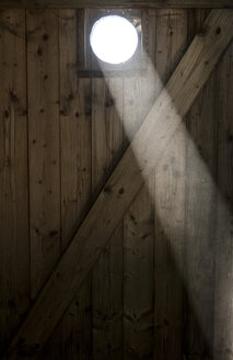 Ray falling through oculus of wooden door - JFEF000732
