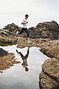 Spain, Ferrol, jogger and his water reflection at the coast - RAEF000575