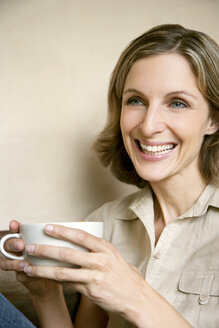 Portrait of smiling young woman with cup of Cappuccino - RMAF000089