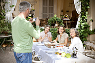 Spain, Mallorca, man taking a picture of three smiling woman in his garden - RMAF000098