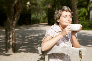 Portrait of mature woman sitting in the garden with cup of Cappuccino - RMAF000101