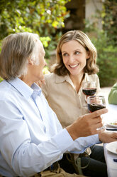 Two friends toasting with red wine in the garden - RMAF000104