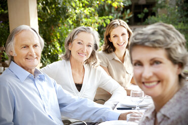 Four smiling friends sitting at laid table in the garden - RMAF000110