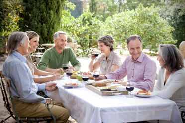Spain, Mallorca, six friends sitting at laid table in the garden communicating - RMAF000119