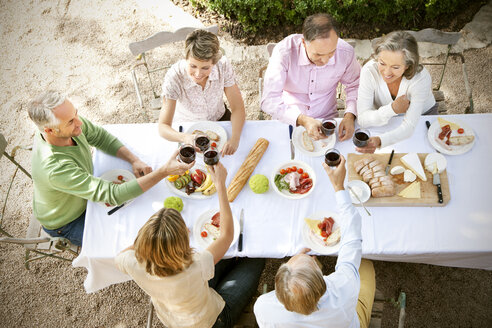 Spain, Mallorca, six friends sitting at laid table in the garden toasting with red wine - RMAF000122