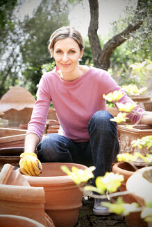 Spain, Mallorca, portrait of smiling young woman gardening - RMAF000125
