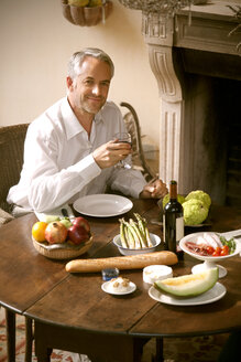 Portrait of smiling mature man sitting at laid table in his living room holding glass of red wine - RMAF000137