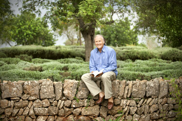 Spain, Mallorca, portrait of relaxed senior man sitting with a book on a wall in the garden - RMAF000149