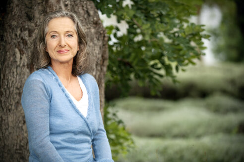 Spain, Mallorca, portrait of smiling mature woman in front of a tree in the garden - RMAF000152
