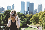 USA, New York City, young woman photographing in Central Park - GIOF000344