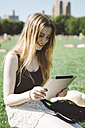 USA, New York City, young woman using digital tablet in Central Park - GIOF000350