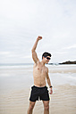 Spain, Galicia, Ferrol, athletic shirtless man on the beach raising his arm - RAEF000593