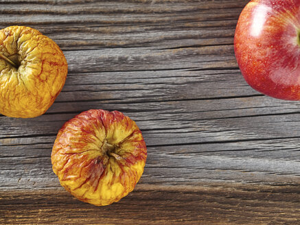 Fresh red apple and a shrivelled one on rough wood - DISF002222