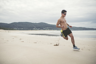 Spain, Ferrol, young man running fast on the beach - RAEF000598