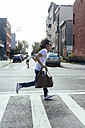 USA, New York City, man in hurry crossing the road in Brooklyn - GIOF000370