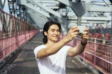 USA, New York City, man on Williamsburg Bridge in Brooklyn taking a selfie - GIOF000376
